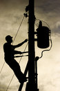 Worker silhouette at a power line post man working on securing transformer Stock Photography