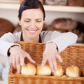 Worker sorting fresh rolls in a bakery smiling happy woman with friendly smile large wicker basket Royalty Free Stock Photos
