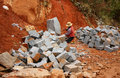 Worker split stone for road works with splitter on hand try to into rectangle shape at mountain pass in lam dong viet nam in Royalty Free Stock Photography