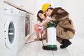 Worker spraying insecticides in front of housewife male insecticide kitchen Stock Photo