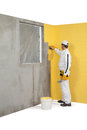 Worker spreading a plaster on a corner wall painted in yellow Royalty Free Stock Photos