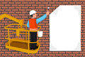 Worker standing in an assembly cradle glues a paper banner Royalty Free Stock Photo