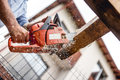 Worker using chainsaw for cutting timber wood, construction material, trimming and slicing logs Royalty Free Stock Photo