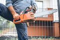 Worker using chainsaw for cutting timber wood, portrait with tools Royalty Free Stock Photo