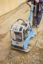 Worker with vibrating plate compactor machine at sand ground compaction Stock Photo