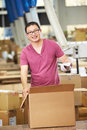Worker in warehouse preparing goods for dispatch male smiling to camera Royalty Free Stock Photography