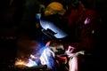 Worker is weld plate by shield metal arc welding