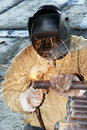 Worker welding with electric arc electrode welder metal by bright and sparks during manufacture of metal equipment Stock Photography