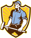 Worker wielding sledgehammer crest retro illustration of a union with hammer done in style set inside shield with sunburst on Stock Image