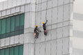 Workers cleaning or painting a multistory building Royalty Free Stock Photo