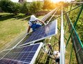 Workers command mounting solar panels on house`s roof. Royalty Free Stock Photo