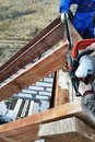 Workers cut the rafters on the roof of the chainsaw house