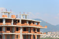 Workers erect balconies from brick in new building at top floor Royalty Free Stock Photography