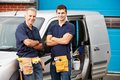Workers in family business standing next to van smiling at camera Royalty Free Stock Photo