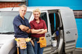 Workers in family business standing next to van smiling camera with arms crossed Royalty Free Stock Images