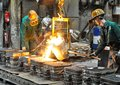 Workers in a foundry casting a metal workpiece - safety at work and teamwork Royalty Free Stock Photo