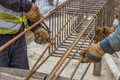 Workers hands fixing steel reinforcement bars at construction site selective focus Royalty Free Stock Image