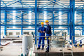 Workers in large metal workshop checking work two or factory standing on machine Royalty Free Stock Photo