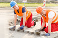 Workers laying cobblestones Royalty Free Stock Photo