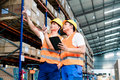 Workers in logistics warehouse at forklift checking list Stock Photography