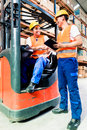 Workers in logistics warehouse at forklift checking list Royalty Free Stock Image