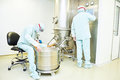 Workers operating pharma fluid bed system pharmaceutical industry pharmaceutical factory granulator dryer and at pharmaceutical Stock Photography