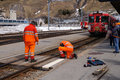 Workers in orange uniform repair railroad , Switzerland Royalty Free Stock Photo