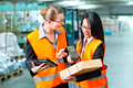 Workers with package in warehouse of forwarding logistics female worker or shipper and employee or colleagues protective vest and Stock Image