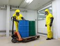 Workers in protective uniforms with barrels of toxic substance uniform mask gloves and boots working chemicals on forklift Stock Images