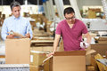Workers in warehouse preparing goods for dispatch male Stock Photography