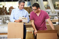 Workers in warehouse preparing goods for dispatch male Royalty Free Stock Photo