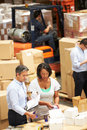 Workers in warehouse preparing goods for dispatch male and female Royalty Free Stock Image