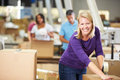 Workers in warehouse preparing goods for dispatch male and female Stock Photos