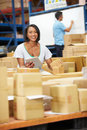 Workers in warehouse preparing goods for dispatch male and female smiling to camera Royalty Free Stock Photo