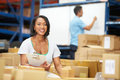 Workers in warehouse preparing goods for dispatch male and female smiling to camera Stock Photography