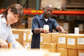 Workers in warehouse preparing goods for dispatch smiling Royalty Free Stock Photography