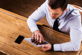 Working at the bar counter top view of confident young man in shirt and tie on digital tablet while sitting Stock Photo