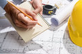 Working on blueprints. Construction project with hands writing o Royalty Free Stock Photo