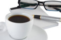 Working environment with pen notebook glasses and a cup of coffee or black tea in white cup Royalty Free Stock Photos