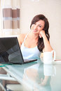 Working at home young woman with a laptop in the living room Stock Photo