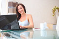 Working at home young woman with a laptop in the living room Stock Image