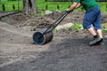 Working with lawn roller gardener uses to make ground plain Stock Photo