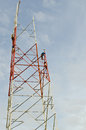 Working men on high pole with blue sky in back Royalty Free Stock Images