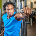 Working out black man in a gym pulling weights on a machine and training his arms Stock Photography
