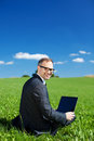 Working out in nature a handsome young businessman sits on the grass a green field on his laptop and looking back at Stock Images