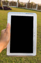 Working in the park hand holding tablet while Royalty Free Stock Photos