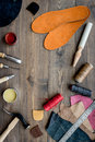 Working place of shoemaker. Skin and tools on brown wooden desk background top view copypace