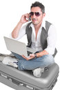 Working on vacation man sitting suitcase talking by phone with laptop Stock Photos