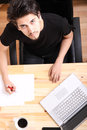 Working on a wooden desk young hispanic man with laptop Royalty Free Stock Photography