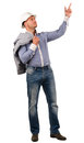 Workman or builder pointing up to blank copyspace wearing a hardhat and carrying a jacket slung over his shoulder standing into Stock Images